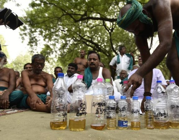 Tamil Nadu Farmers with urine filled in bottles.